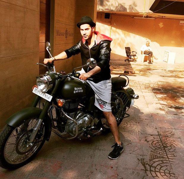 वरुण धवन अपनी बाइक पर पोज देते हुए