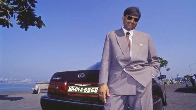Harshad Mehta posing next to his Toyota Lexus