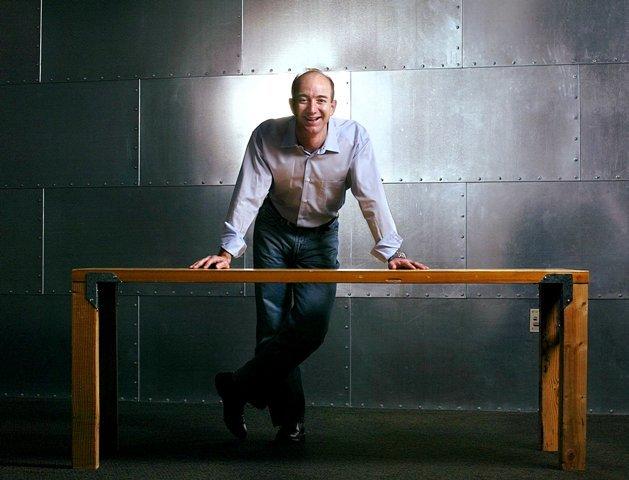 जेफ बेजोस उस टेबल के साथ पोज देते हुए जिसे उन्होंने एक दरवाजे से बनाया था
