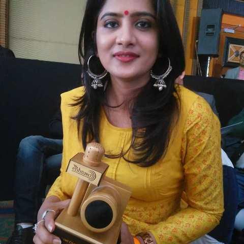 Neha Batham holding an award